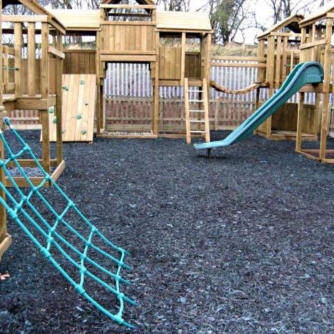 Blue mini rubber chippings in a playground setting
